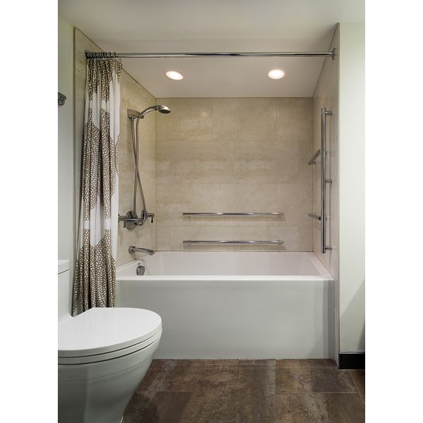 TAKE HOLD. A deep soaking tub with mounted and handheld showerhead gets extra-long grab bars—both horizontal and vertical—for added stability. Sleek and stainless bath fittings are as attractive as they are practical.
