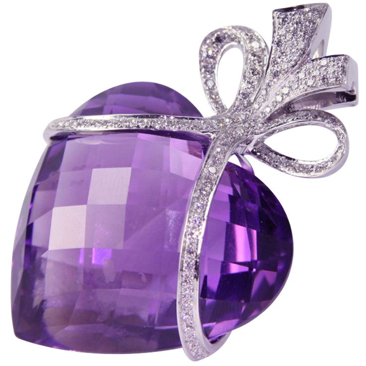 Beautiful Amethyst Heart enhanced by a Diamond encrusted Bow, suspending from a 17inches white gold chain. Wow! Handmade in 14k White Gold; amethyst heart weighs approx. 125 ct; one hundred twenty-two diamonds weigh approx. 1.25ct; heart size, including diamond bow: 2.5x1.5 inches. Circa 2000s