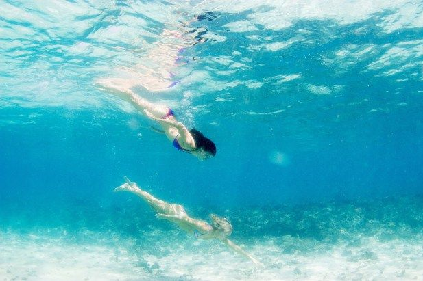 underwater two women in clear Fiji water at Cloud 9 by Anais Photography