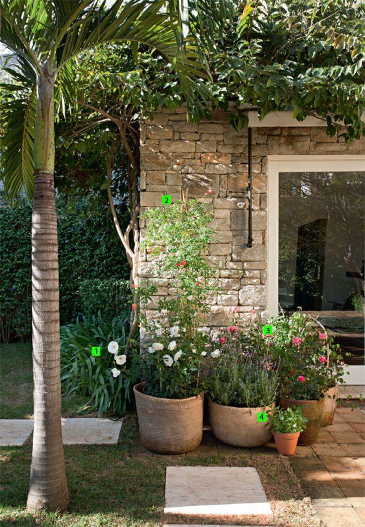 """VASOS DÃO CHARME: apesar de haver lugar de sobra para canteiros, o paisagista preferiu dispor a maioria das variedades em recipientes de barro (Jardí). """"Eles já ornamentam o jardim. Além disso, como limitam o crescimento das plantas, estas exigem menos podas"""", diz Gilberto. Aparecem rosas brancas (Rosa alba L.) (1), minirromã (Punica granatum 'Nana') (2), rosas híbridas da variedade Milrose (3) e manjericão (Ocimum basilicum) (4)."""