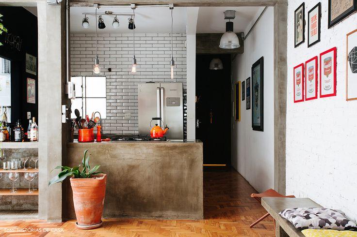 Cozinha industrial tem bancada de concreto armado e revestimentos de subway tiles.