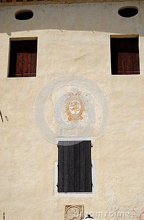 Photo made at a very elegant facade of a building in Portobuffolè in the province of Treviso in the Veneto (Italy). In the image you see three windows with closed wooden shutters. they form the vertices of a triangle with the base at the top and center of which is a painted coat of arms. Under the pitch of the roof and in the shade band you see two ovals lying.