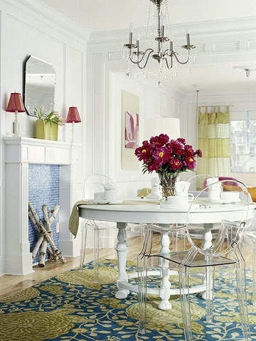 Dining room with floral patterned rug and lucite chairs.