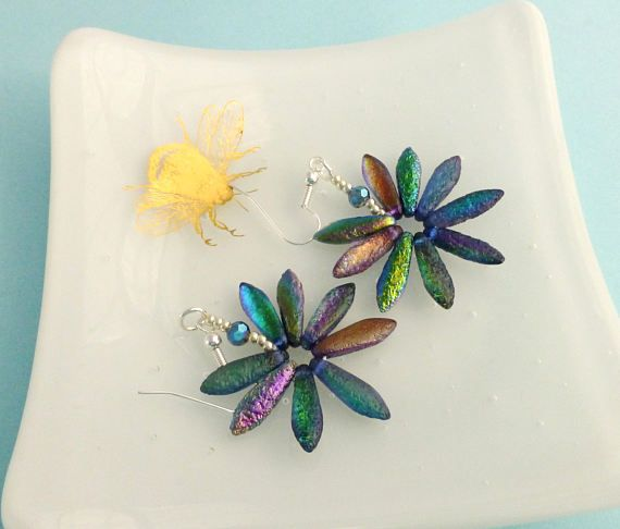 These beautiful, colourful daisies are hand stitched from really lovely czech glass dagger beads in a gorgeous etched metallic glass. They shine in pretty blues and greens mainly, but have all the colours of the rainbow as they catch the light. I finished the look with silver seed beads and coordinating crystals. These would look fab for a summer festival and are sure to be noticed!  The daisy measures approx 3cm Option of either silver plated or sterling silver earwires.  These can be made…