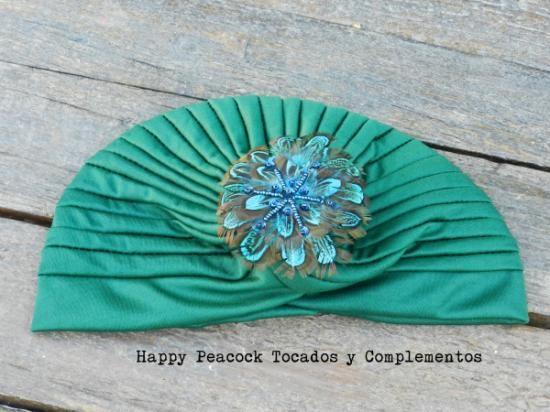Turbante de lycra en verde monte con adorno de plumas de pavo real y cuentas de resina.