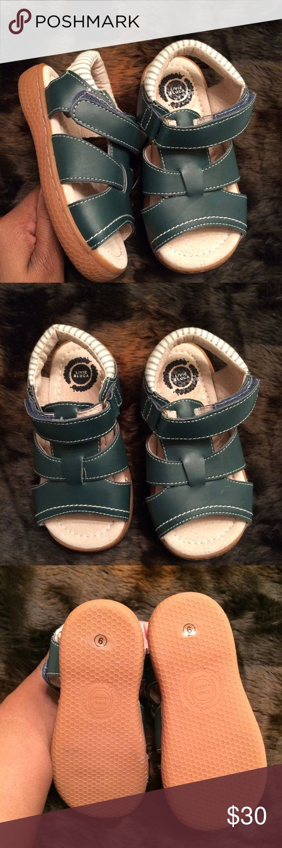 Livid & Luca Sailor Sandal These sandals are well made and perfect for your little man! They are composed of soft leather which makes them durable enough for even the most active baby boy! They feature soft foot beds as well as padded ankle straps designed to give him the most comfortable fit! Add these to his collection today! ‼️‼️The website describes them as vintage blue but I get hints of a nice deep Forrest green color 🤷🏾♀️ Livie & Luca Shoes Sandals & Flip Flops