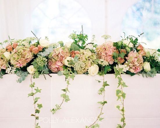 Smaller in size perhaps reversed colour, cream hydrangeas and blush roses. Like the trailing ivy. Use for two tables in ceremony room then relocate to top table.