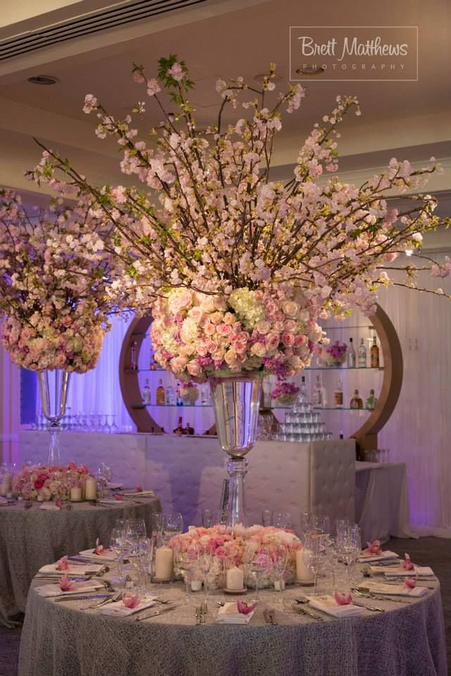 Large table centerpieces.  Includes a large cluster of hydrangeas accented with large blooms - such as football mums.  Eucalyptus  spilling over edge with gold accents. Flowering tree branches on top.  Colors are cream, peach, salmon and blush tones.