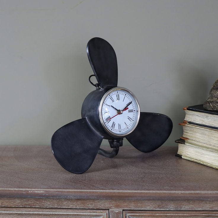 Black Metal Propellor Desk/Mantel Clock Retro style propellor clock, perfect for displaying on your desk, shelf or mantelpiece Fantastic little clock that adds a nautical theme with clock face nestled in a propellor shape frame With little stand at the back to keep it steady and Roman Numerals on a white clock face, perfect gift for dads and boys Takes x1 AA battery