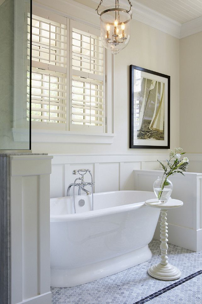 White shutters, a free-standing tub, painted panelling and a framed black and white photo - some of the ingredients for a classic New England bathroom designed here by Muskoka Living (muskokalivinginteriors.com)