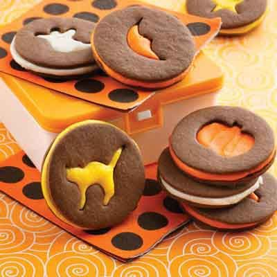 Vanilla buttercream filling highlights Halloween designs in these chocolate cut-out sandwich cookies.