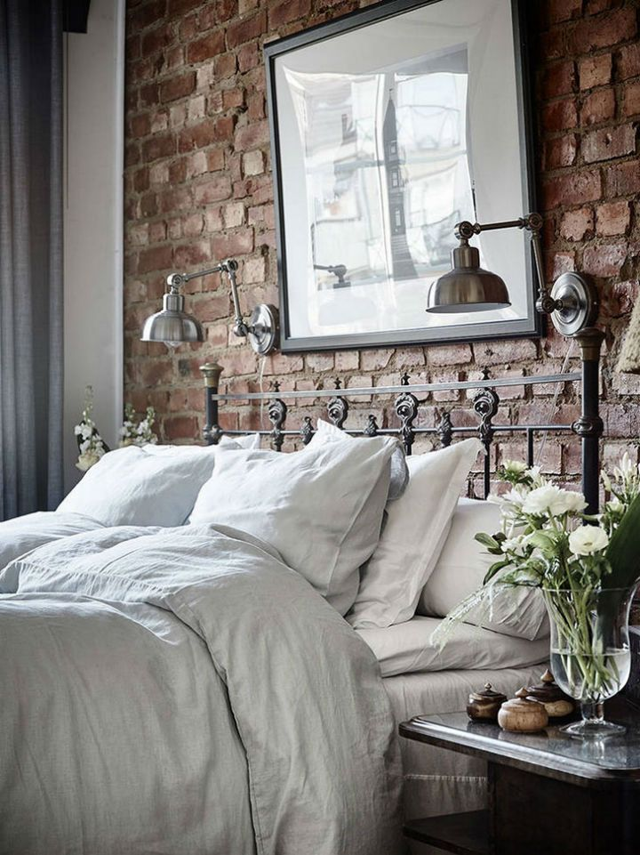 Beautiful bedroom design with red brick wall, antique bed and some wall art above the bed