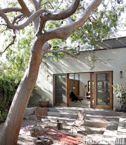 The interior courtyard is visible from almost every room and makes a medium-size house feel much more spacious. Rocks and stones suggest a Japanese garden. Amphitheater-style steps provide extra seating when the owners are having a party. Exterior sconces by Robert Lewis for Commune.