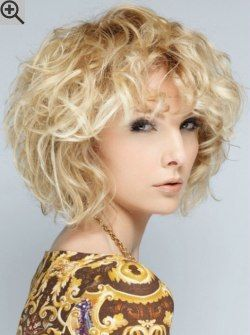 Angled chin length bob with curls and curly bangs. Blonde hair with highlights.