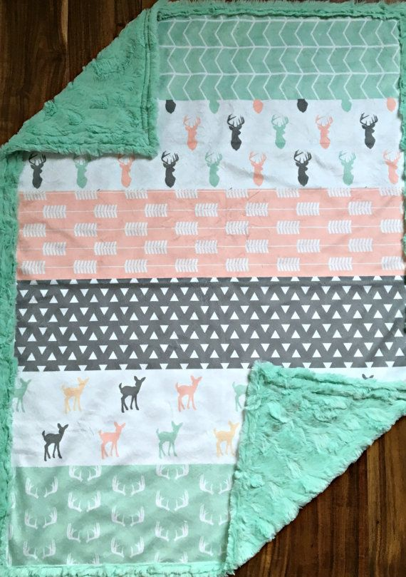 This baby blanket has minky on both sides. The front side is one solid piece of designer minky. It has strips of fawns, triangles, arrows, antlers