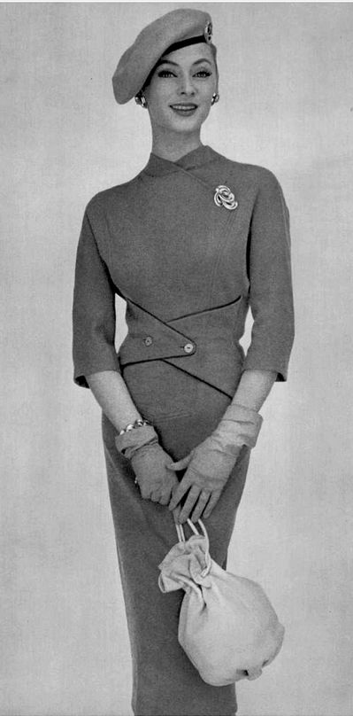 1956Ghislaine Arsac in lean, elegant, beige jersey dress, with triangular buttoned tabs that emphasize the waist, by Manguin, beret by Paulette, leather drawstring purse by Winter, photo by Pottier. What I like here is the waist detail. Could be fun to make a belt like that.