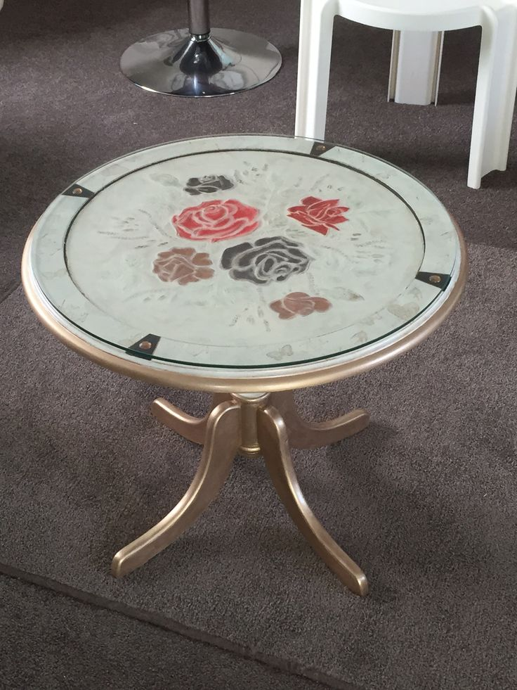This is a commission piece., the table was a very dark brown with a copper insert. My client wasn't keen on the colour or the copper, and gave me complete freedom to restyle this piece. The room this was going in was a bedroom, which contained a cream and gold dresser and a bedspread with huge red roses and black accents. That was my inspiration