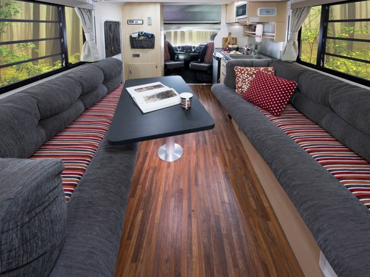 The lounge/dining area of theLeura motorhome when the electric roll down bed is in the raised position. Can you picture yourself relaxing on the lounge?