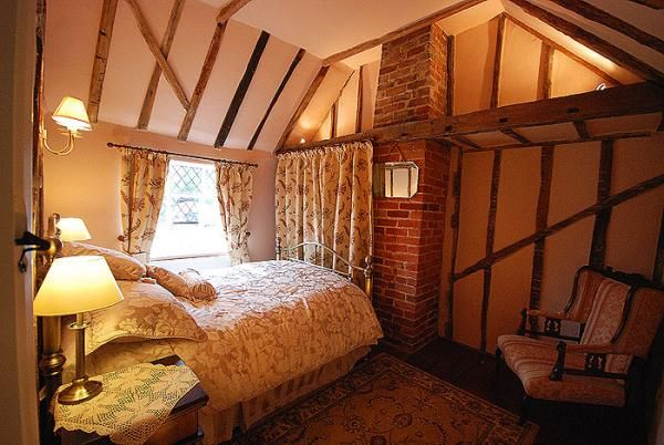 The delightful master bedroom has exposed beams and brickwork which gives the room and the cottage beautiful character
