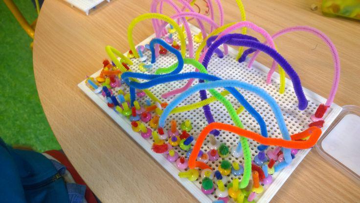 Exemple de création avec des cures pipes, petits boutons et les planches du jeux à clou en plastique