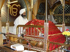 A Granthi reciting from Guru Granth Sahib.    Sikhpoint.com