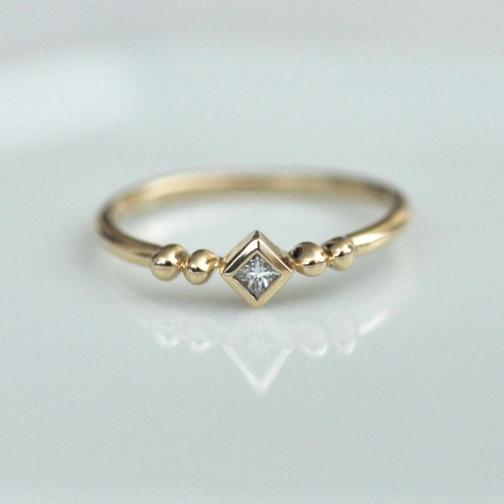 This Little Square Diamond Ring by Porter Gulch features a stunning bright-white diamond and beautiful beading detail.