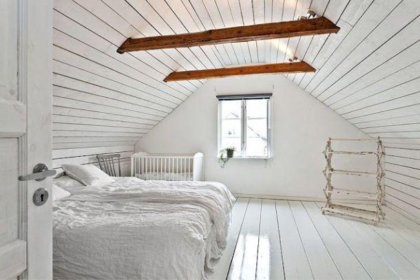 biala sypialnia na poddaszu z drewnianymi belkami