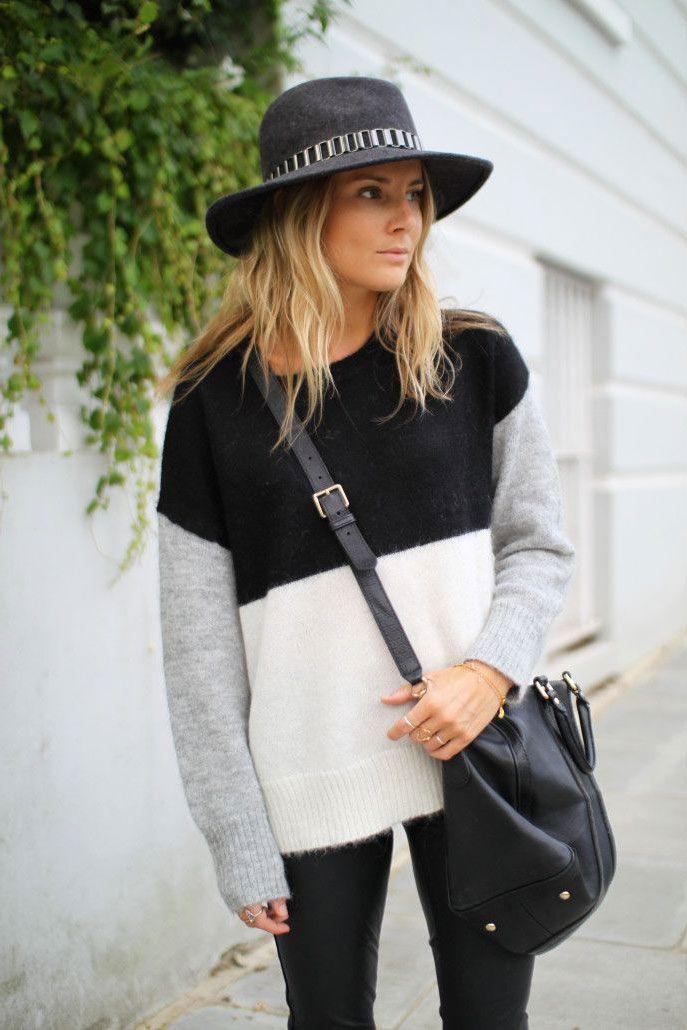 Street style look suéter preto e branco, calça preta e chapéu cinza.