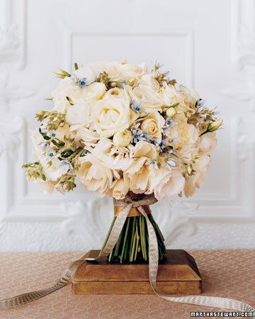 Velvet-stemmed Tweedia add that something blue to a white-on-white bouquet of spray and tea roses, Lisianthius buds and flowers, and Ranunculus. A slim metallic-silver vintage ribbon lends a touch of sparkle.