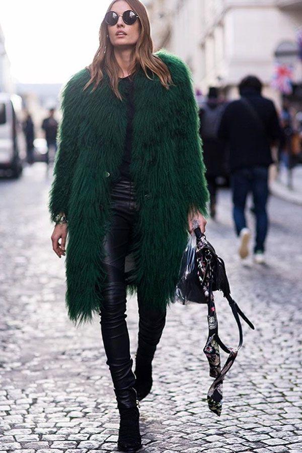 Street style look maxi casaco fluffy coat verde, calça preta de couro, blusa preta e botas.
