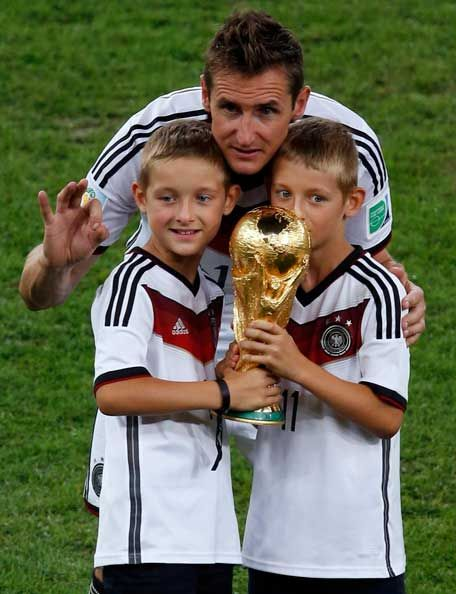 Germany's Miroslav Klose and his sons pose with the World Cup trophy after winning their 2014 World Cup final against Argentina