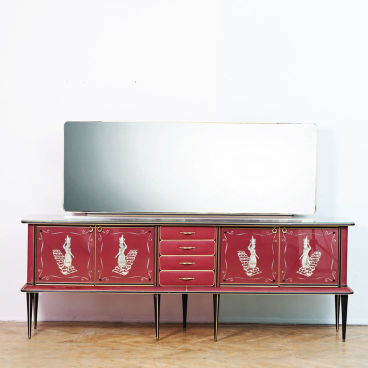 Designed by UMBERTO MASCAGNI  Manufactured by UMBERTO MASCAGNI  ITALY  Circa 1950  This credenza was designed by Umberto Mascagni for Mascagni Co. Bologna in the early 1950s, but sold by Harrods throughout the 1960s and 1970s. It consists of two doors with reverse painted glass fronts and details of a woman walking down the stairs baring a pitcher of water and four drawers in the middle. The main body structure is made from solid wood and also features a large mirror in excellent vintage…