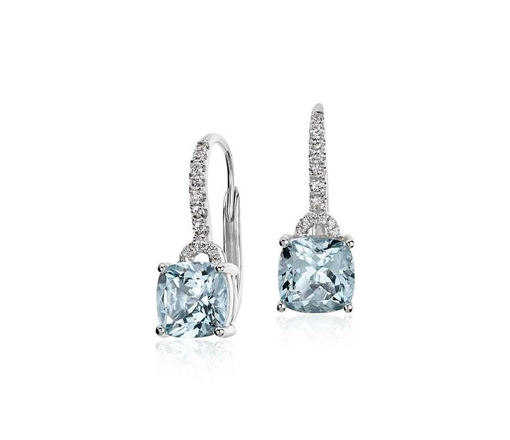These drop earrings feature beautiful cushion cut aquamarine gemstones framed with round brilliant diamonds in 14k white gold.