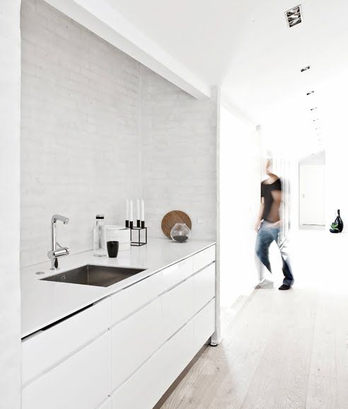 WHITE Kitchen Interior ::   Painted white brick wall.   Seamless white benchtop.    Gentle white wash oak floor boards.  Corian Kitchen