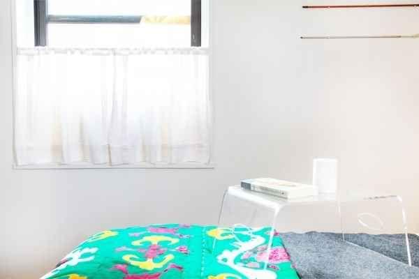 Para una unidad de aire acondicionado de ventana, colgar cortinas de estilo cafetería en una barra de tensión.