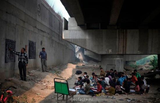 Малообеспеченные индийские дети обучаются в бесплатной школе под мостом метро в Нью-Дели, Индия. По меньшей мере, 30 детей, проживающих в близлежащих трущобах, получали бесплатное образование в этой школе за последние три года.