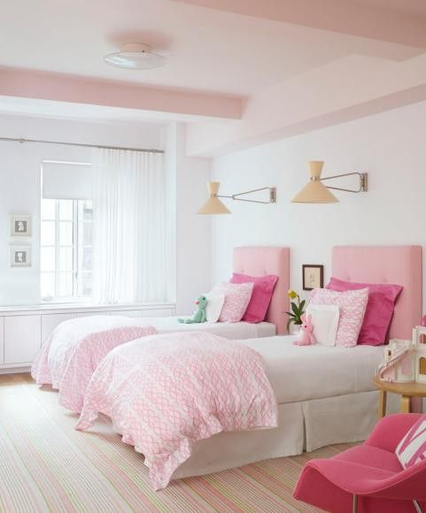 This lovely pink girl's room is made more interesting with modern lamps and a vintage modern chair in hot pink.