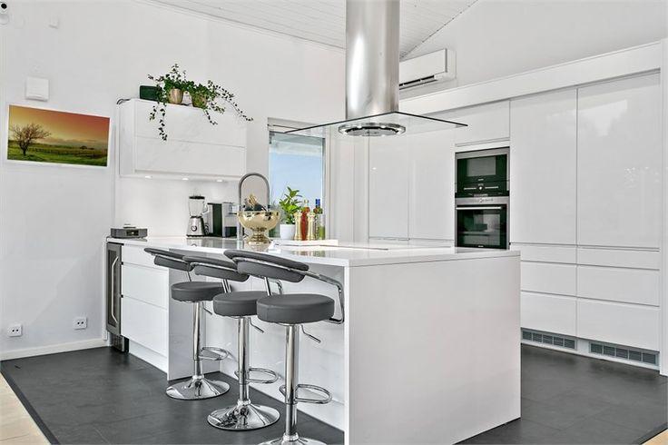 En stor kökshalvö och en skåpsvägg med beslagsfria fronter i högglansig vit ger köket en stilren design. Line vit högblank | Ballingslöv