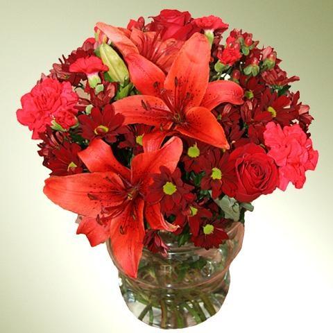 preciosa combinacin de flores variadas en tonalidades rojas ms de flores como margaritas gerberas claveles liliums y acompau