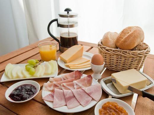 Das deutsche Frühstück - Kaese, Brot, Wurst, Saft, Kaffee oder Tee, Marmalade, Eier, und frisches Obst. German Breakfast.
