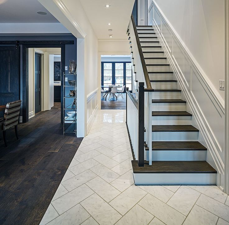 foyer with dark stair treads, white risers, dark railing, white spindles, wainscot, while marble herringbone floor