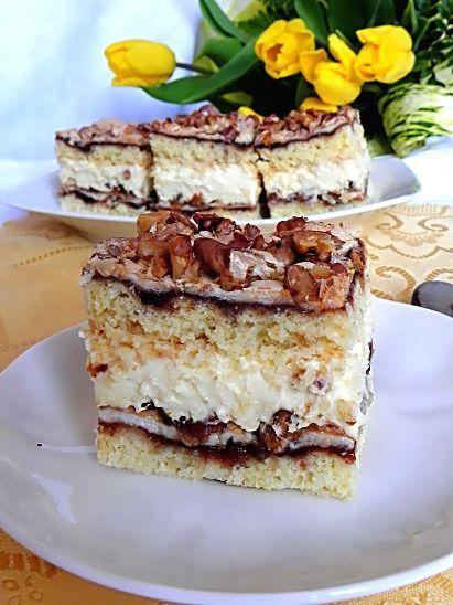 Dwa kruche placki z delikatną, słodką bezą, obsypaną chrupiącymi orzechami, przełożone kremem, a całą słodycz ciasta przełamują delikatnie powidła śliwkowe!!