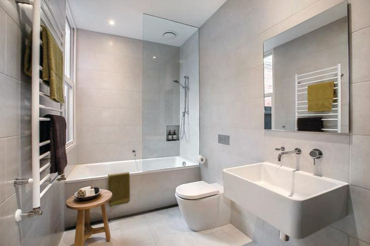 Wall and floor tiles, light grey, shower over bath, touch of timber.