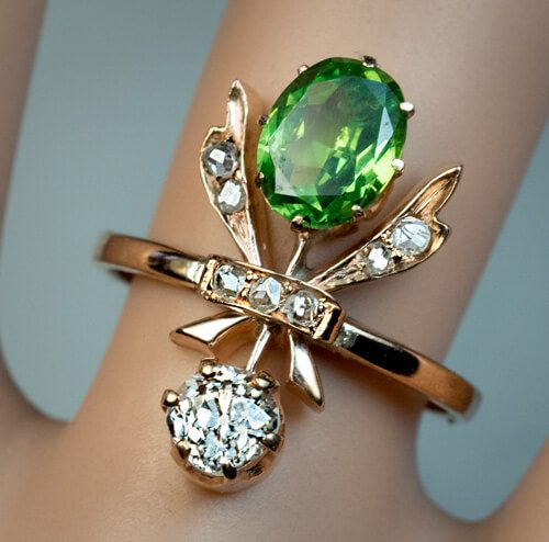 Russian, made between 1899 and 1908 A 14k gold ring is designed as a stylized flower or a fly. The ring is set with one1.22 ct Russian demantoid of excell