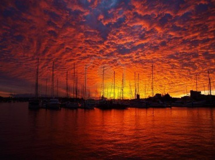 Stronly coloured blood red sunset highlighting Altocumulus cloud formation at a marina at Mooloolaba-Queensland-Australia -With water forground. Stock Photo