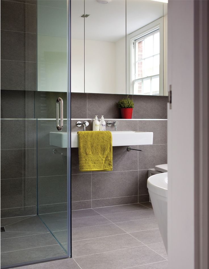 curbless shower with large format tiles on floor and wall. Floating vanity