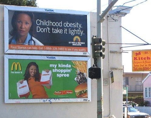 An example of juxtaposition where an advert for junk food is located alongside an advert against obesity.