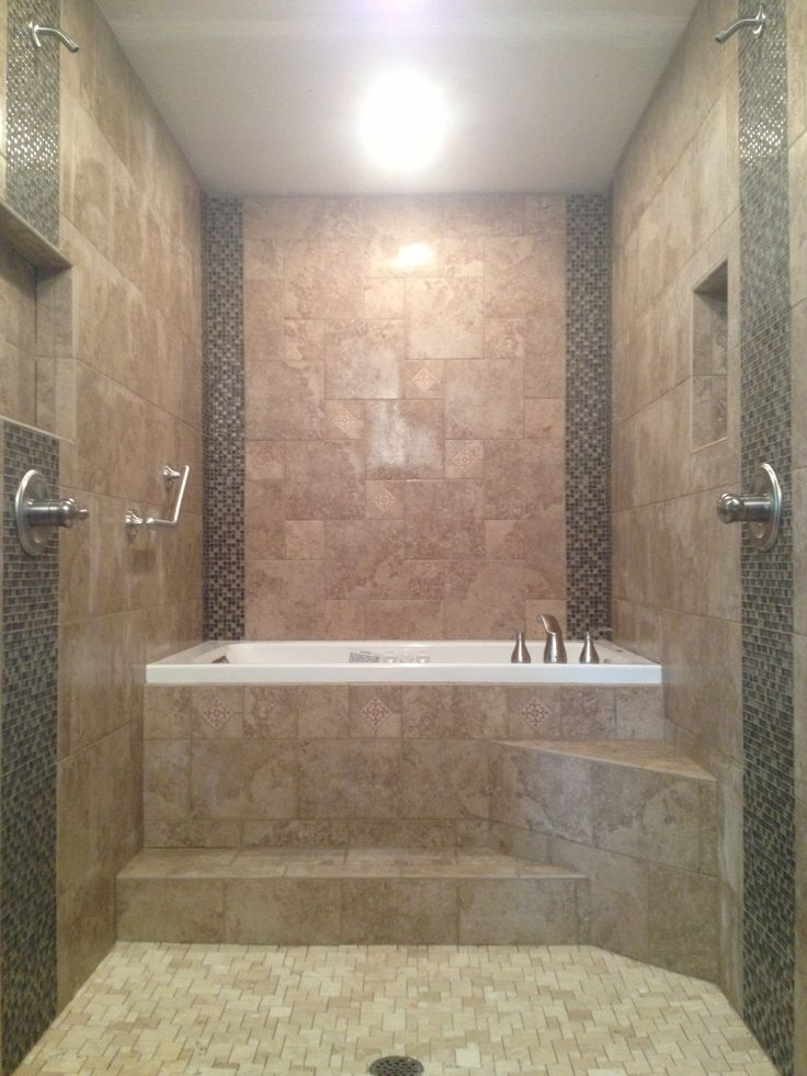 Master Bathroom renovation. Walk through dual head shower to a raised drop in Jacuzzi whirlpool tub. All porcelain tile with glass and natural stone mosaic accent. Travertine stone mosaic shower floor. Beautiful. Looks better than imagined.