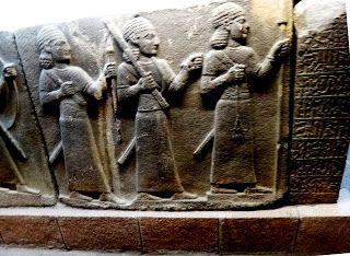 Escultura em alto-relevo em pedra basáltica do período Neo-Hitita. Três figuras com cabelos cacheados e longas túnicas e largos cintos. O personagem da frente sustenta uma lança que está quebrada em um dos lados  na mão esquerda e um ramo com folhas na sua direita.  O personagem do meio aperta o seu punho direito e segura uma ferramenta na altura da cabeça na sua mão direita. Eles são seguidos por um personagem que carrega um bordão ma sua mão esquerda . Todos os três usam longas espadas na…