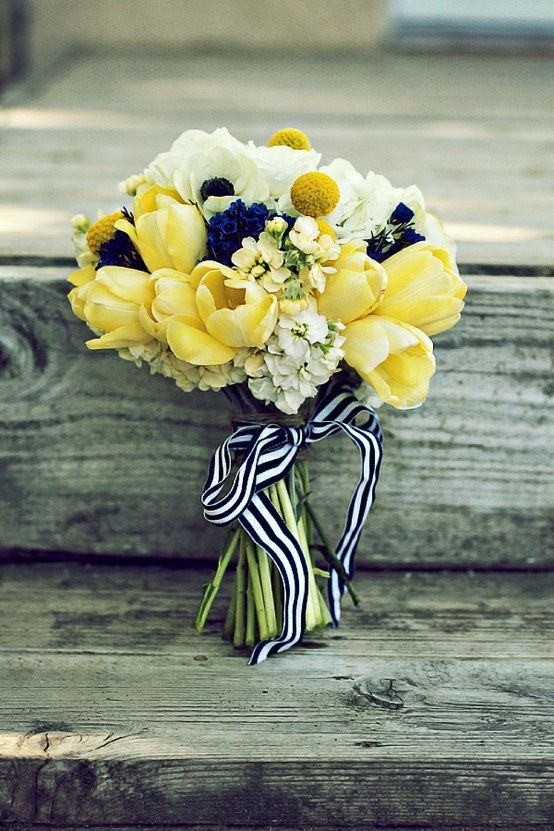 Yellow tulips are combined with bright yellow billy balls, creme and butter stock, and bright blue scabiosa. Perfect for a navy and yellow wedding.